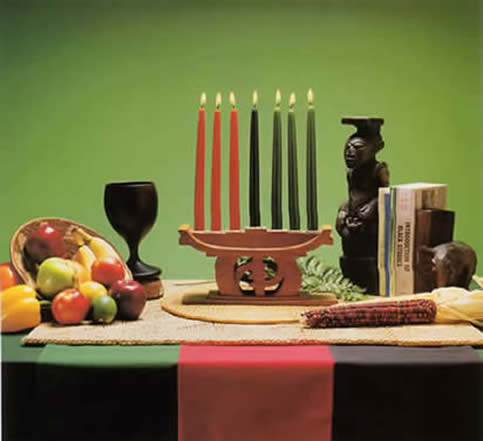 A Kwanzaa table arrangement includes fruits and vegetables, ears of corn, a mat, the unity cup, gifts, candles, and a kinara (Image borrowed from the Official Kwanzaa Website)