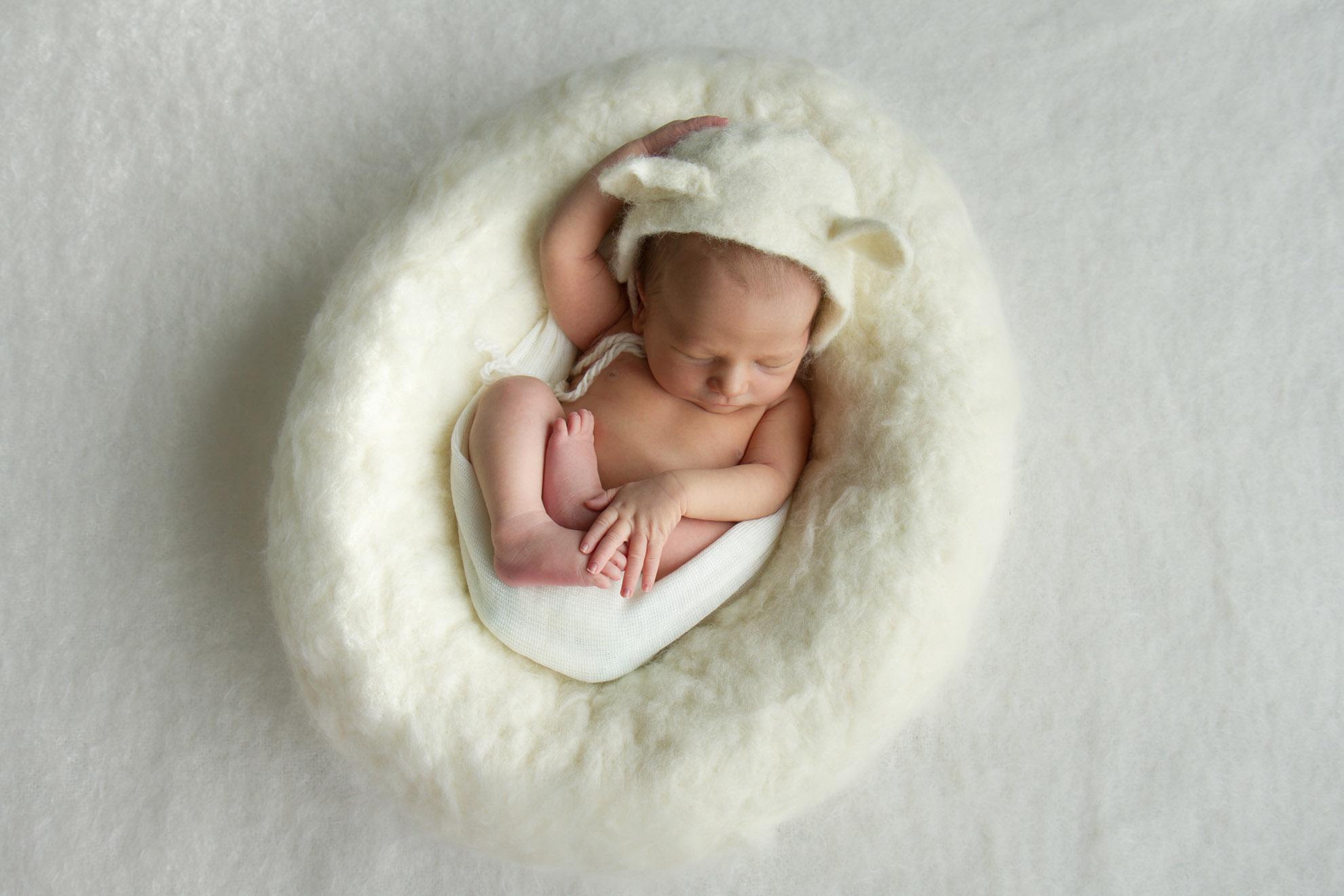 Hamilton-photographer-newborn-in-wool-nest-with-lamb-hat.jpg