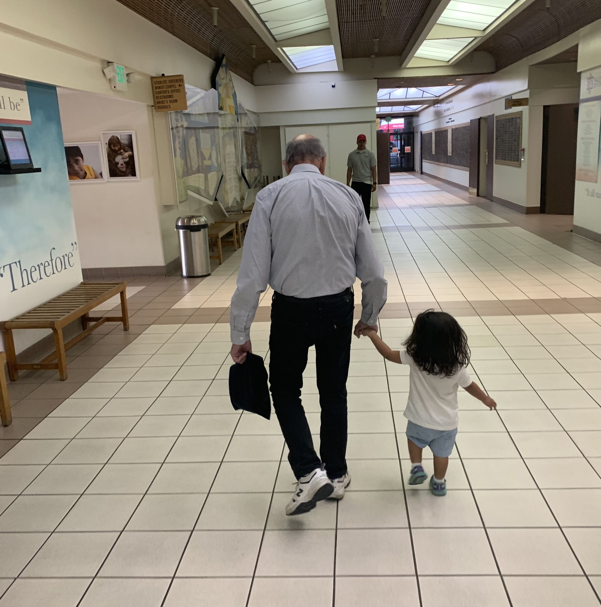Papa and our daughter walking through Valley Beth Shalom to the service for the Fast of the First Born.