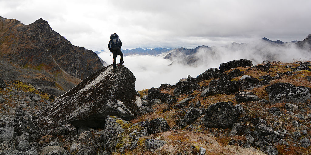( A hiker perches above the clouds in the Talkeetna Mountains of Alaska  | Paxson Woelber)