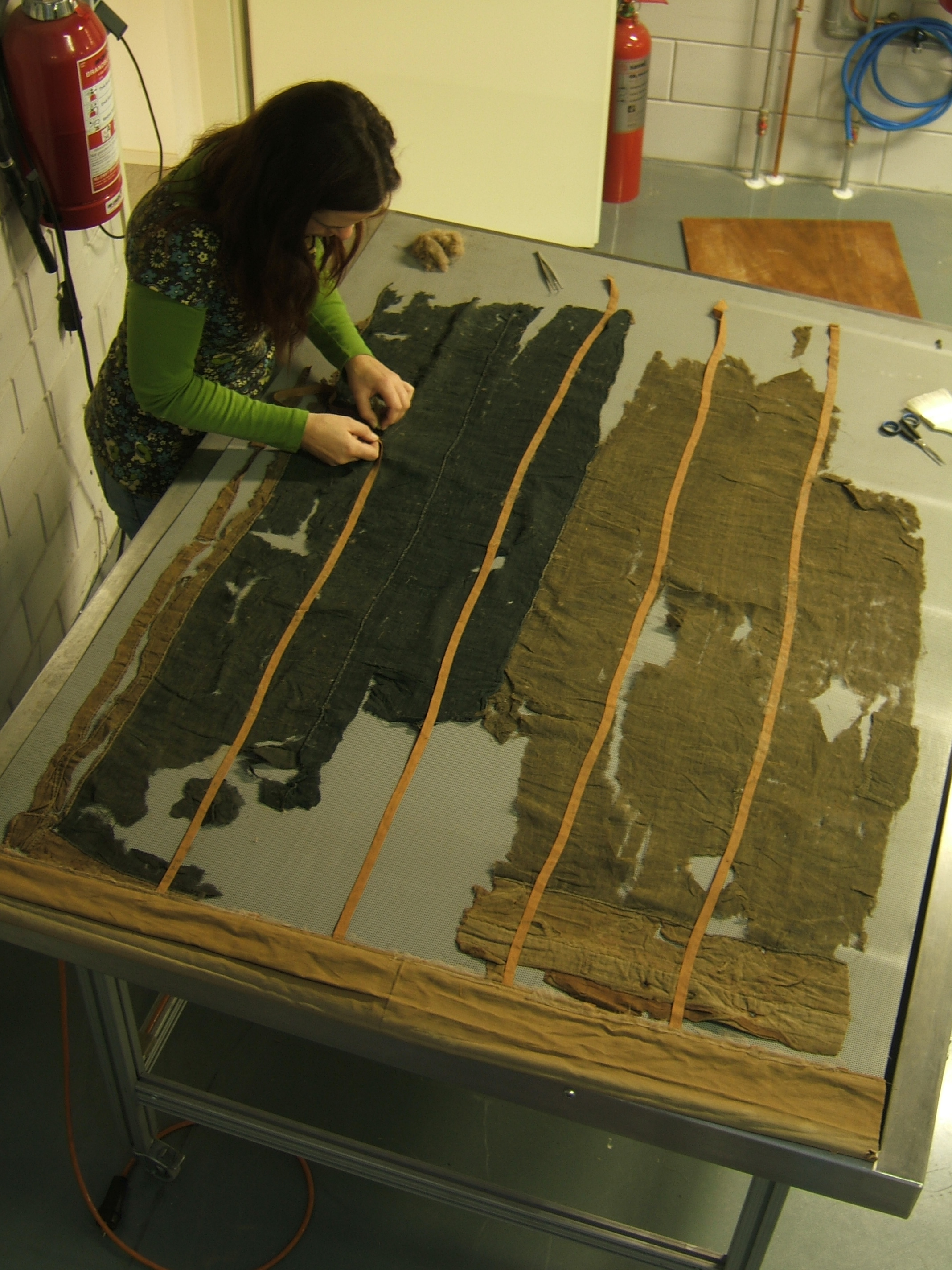 cleaning a 18 th  century flag on the vacuum table