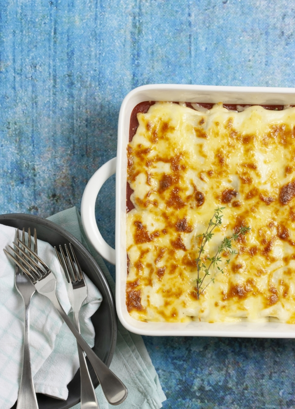 Steam oven spinach, ricotta and mushroom cannelloni in a white baking dish with blue background and cutlery to the side