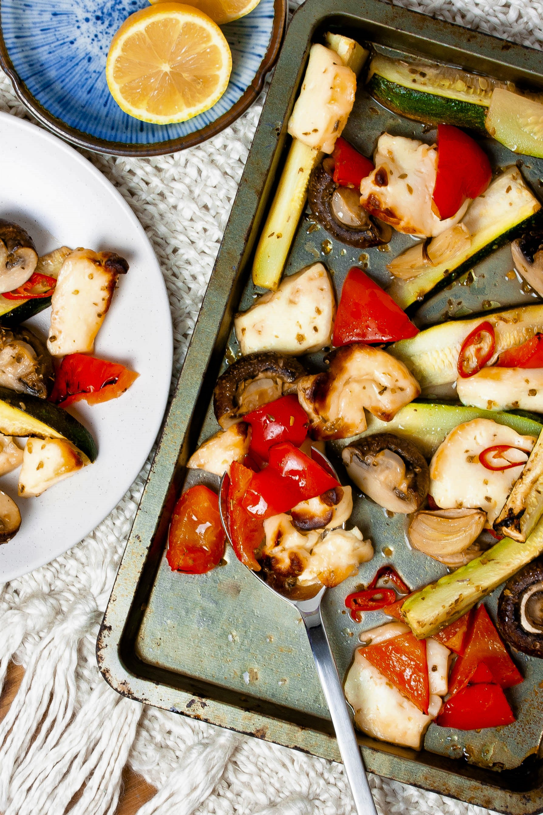 Steam oven baked haloumi cheese, red peppers, zucchini and chilli, served from a metal pan with a blue dish of lemon halves at the side.