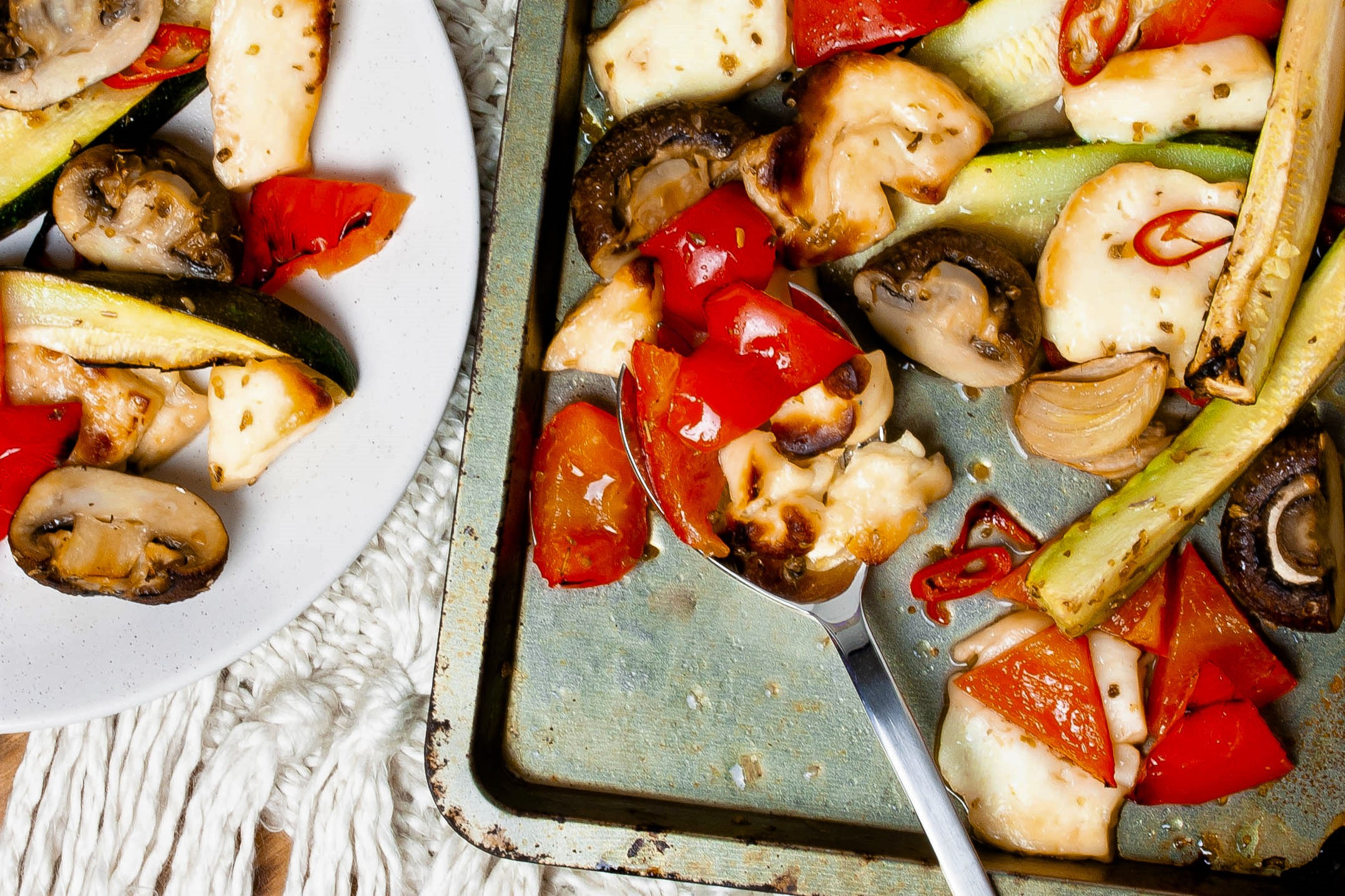 Haloumi cheese, red peppers and courgettes with fresh chili and garlic, roasted and served from a metal pan.