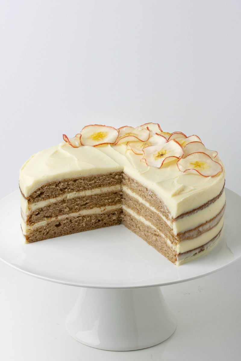 A three layered apple spice cake with cream cheese frosting, with a wedge cut out, decorated with candied apple slices and served on a white cake stand