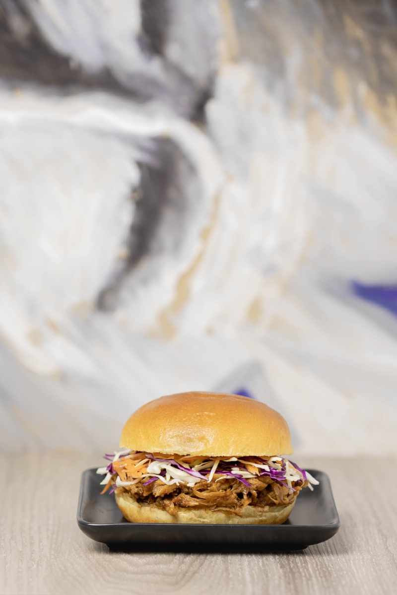 Steam oven pulled pork on a brioche roll, with slaw, served on a black ceramic dish.