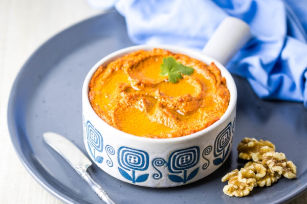 Muhammara, Syrian roasted red pepper and walnut dip, served in a blue flower-patterned dish with parsley on top and extra walnuts to the side.