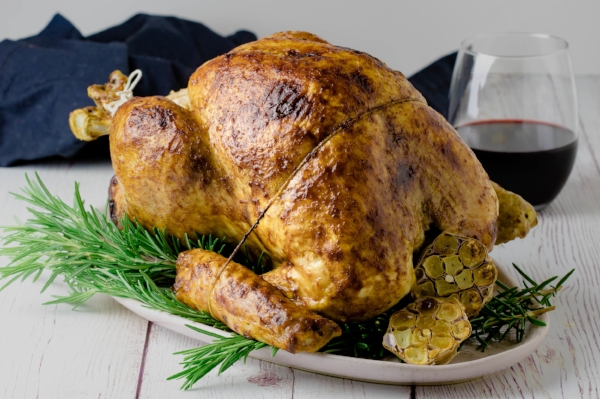 Whole roasted turkey, cooked in a steam oven. Presented on a large platter with rosemary and roasted garlic, ready for carving.