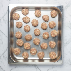 Oven baked meatballs, formed and raw in the pan.