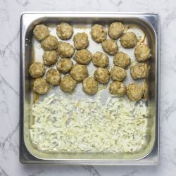 Oven baked meatballs, browned with onions added to the pan.