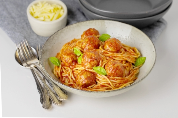 Oven baked meatballs and tomato sauce, served in a large shallow bowl with spaghetti and basil leaves, with cheese to the side.