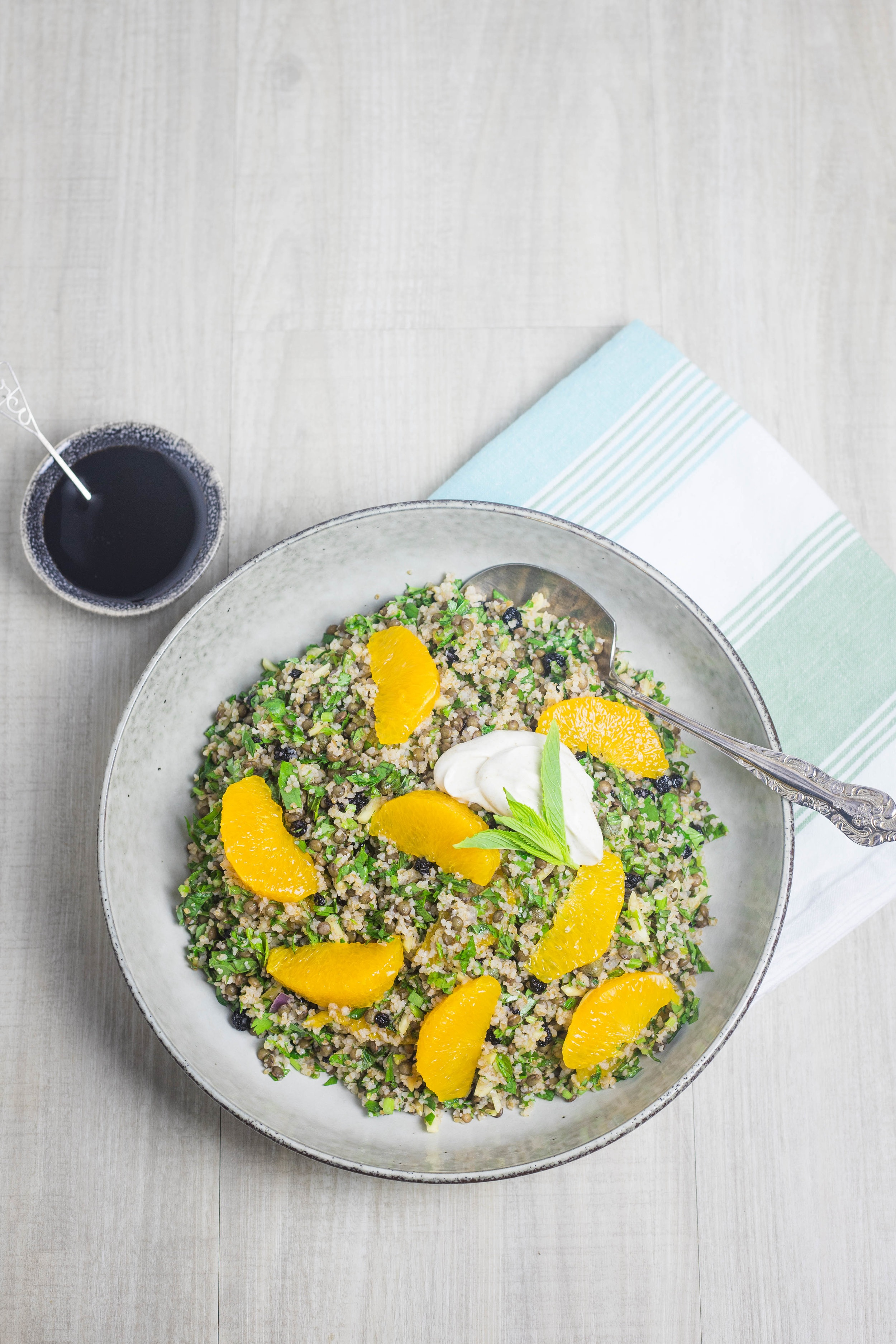 Lentil, cracked wheat, herb and orange salad served in a stoneware bowl with a serving spoon. Pomegranate molasses and cumin yoghurt served on the side.