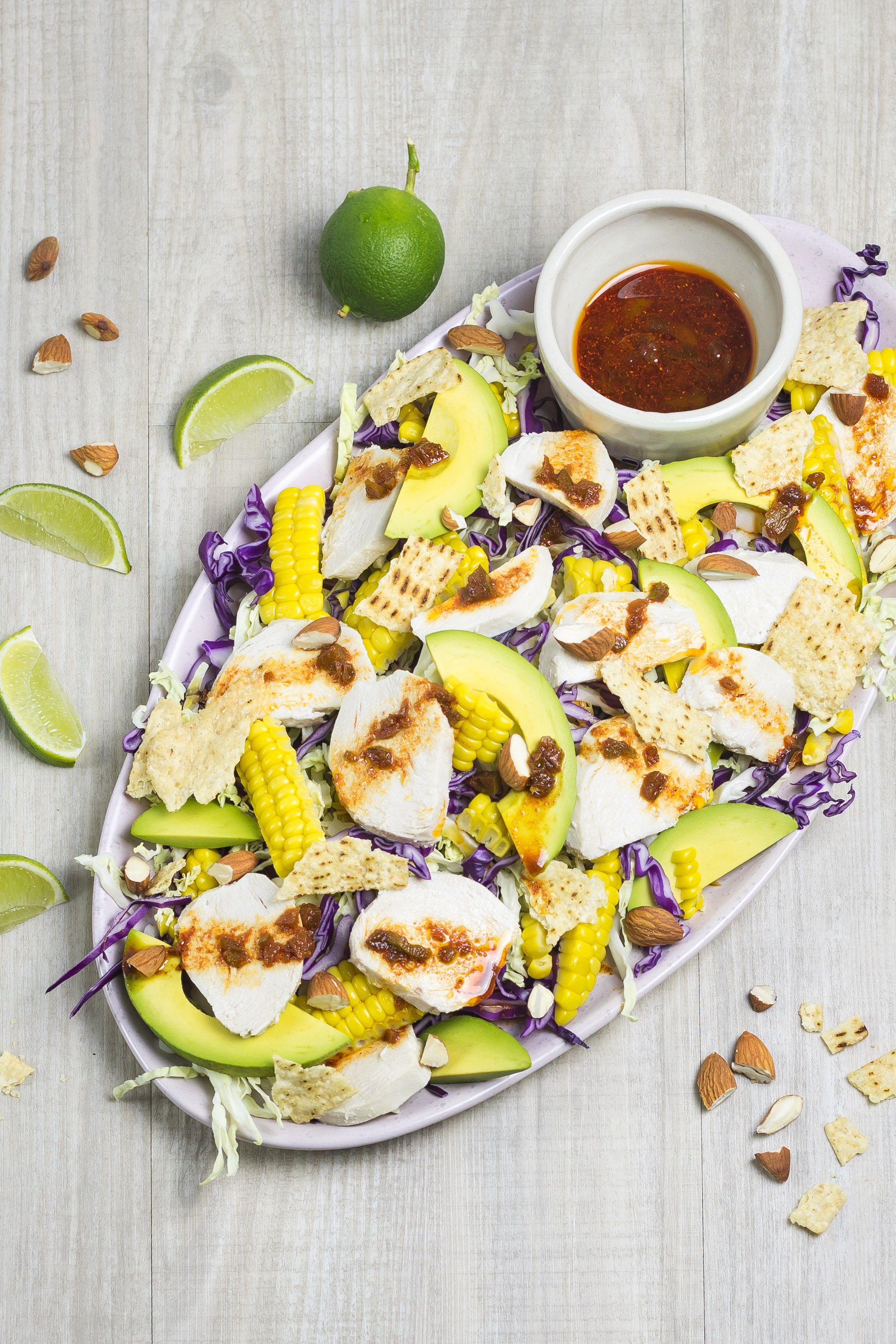 Mexican poached chicken salad ready to serve on an oval platter, with jalapeno dressing, lime wedges and tortilla chips over the top.
