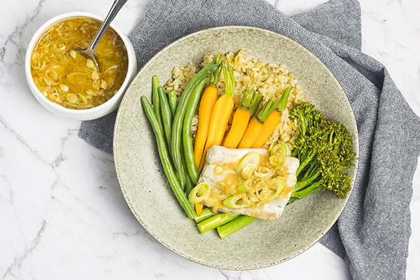 Easy steamed fish dinner with vegetables, brown rice and miso ginger dressing, presented in a bowl with a grey napkin alongside.