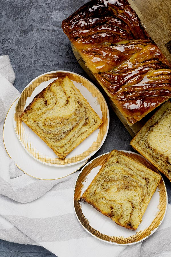 Twisted cinnamon bread slices served on gold-rimmed white plates, resting on a beige striped dish towel.