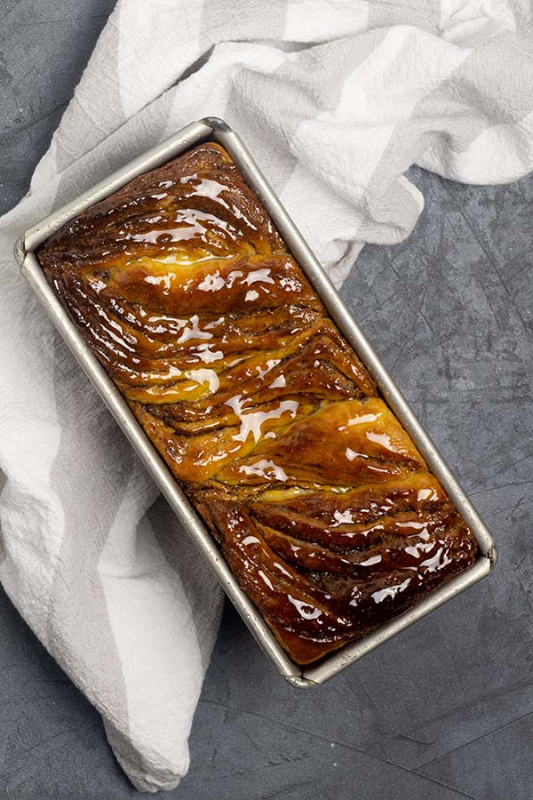 Twisted cinnamon bread, glazed and sitting in a loaf pan atop a beige striped dish towel.