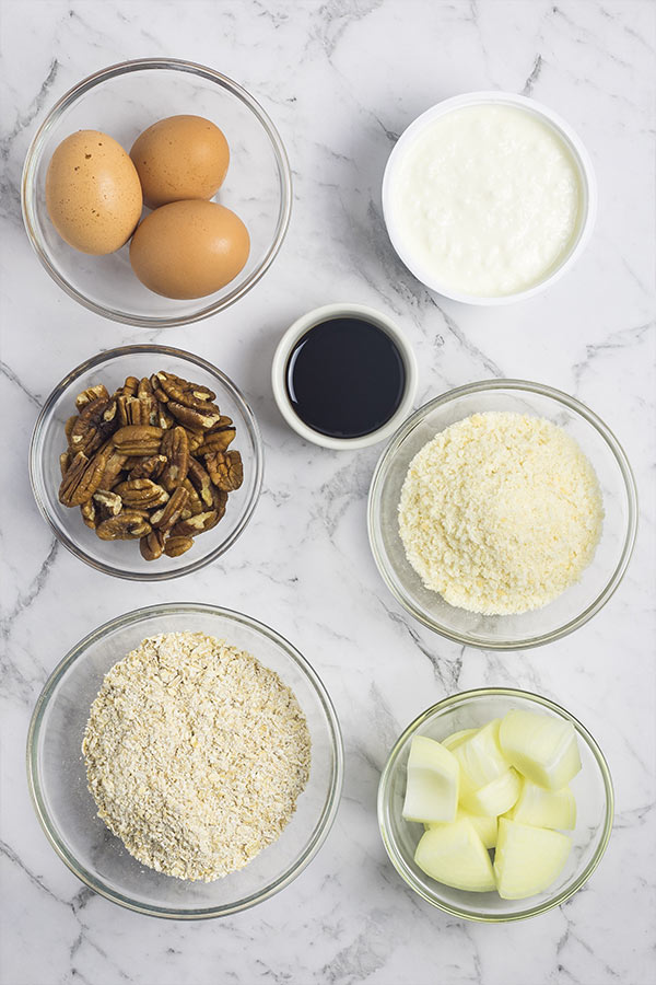 Ingredients to make vegetarian sausage rolls: eggs, cottage cheese, pecan nuts, soy sauce, breadcrumbs, oats, onion.
