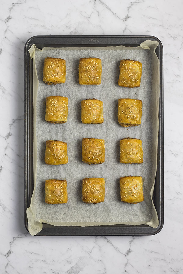 Baked vegetarian sausage rolls on a parchment-lined baking tray.