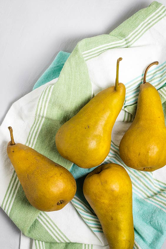 Four washed fresh pears on a dishcloth