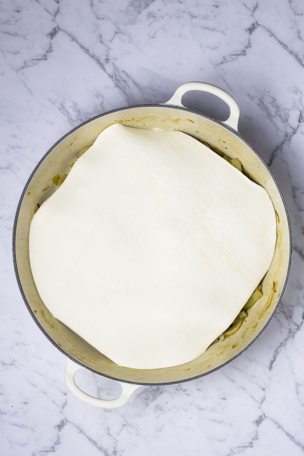 Uncooked puff pastry, laid over the top of leek and mushroom tart mixture in a pan, ready to bake.