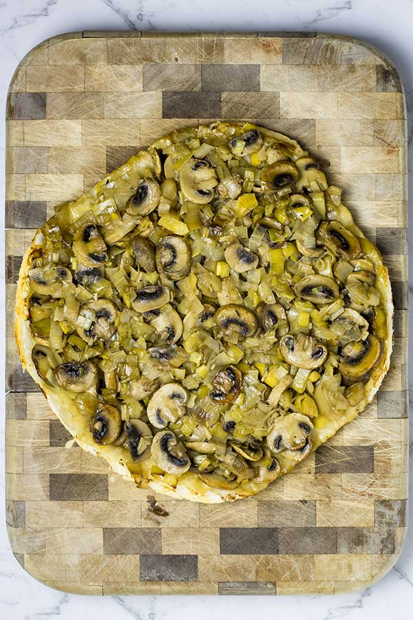 Upside down leek and mushroom tart on a chopping board, ready to slice and serve.