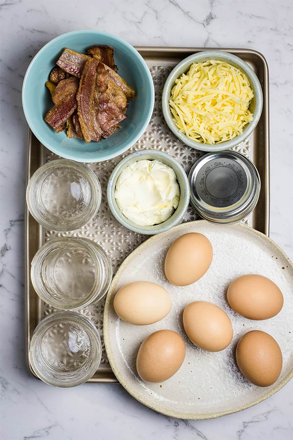 Ingredients for sous vide egg bites on a tray: eggs, cheese, cream cheese and cooked bacon