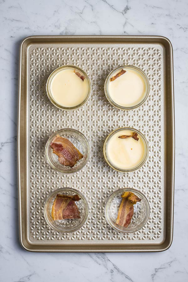 Sous vide egg bites jars, with bacon strips and egg filling poured in