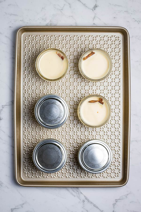 Sous vide egg bites ready to cook. 6 filled jars on a tray, 3 with lids on