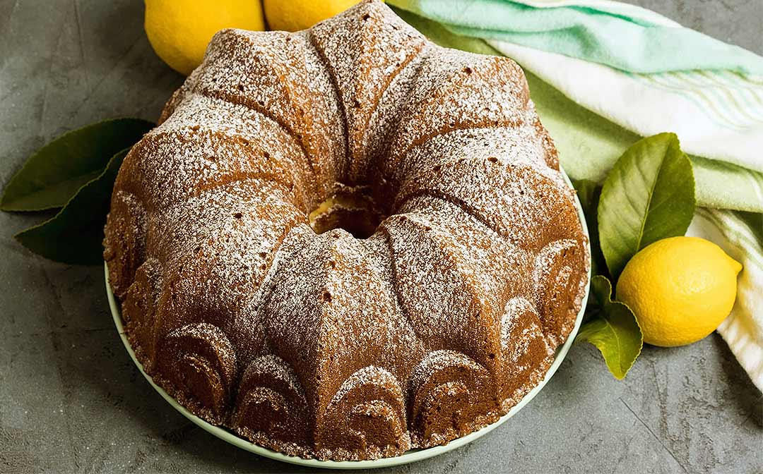 A whole cream cheese pound cake on a plate, surrounded by fresh lemons, lemon leaves and a green striped kitchen towel.