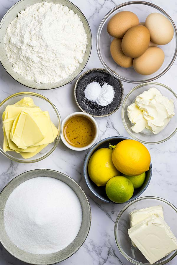 Ingredients for cream cheese pound cake: flour, eggs, sour cream, lemons and limes, cream cheese, sugar, butter, vanilla, baking powder and salt.