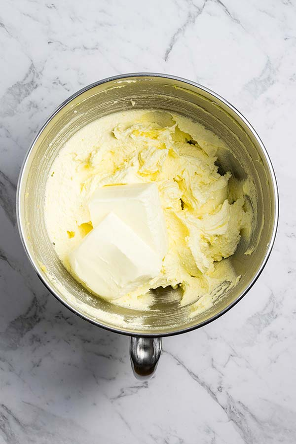 Creamed butter and sugar in a bowl, with cream cheese sitting on top ready to be mixed in.