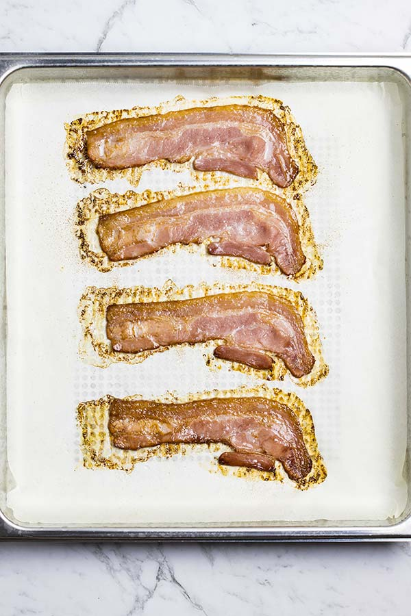 Cooked slices of bacon in a baking-paper-lined pan.