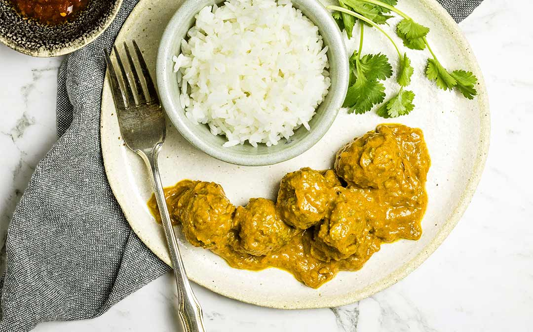 Chicken meatball curry served on a white stone plate, with a dish of rice and a bowl of chilli alongside.