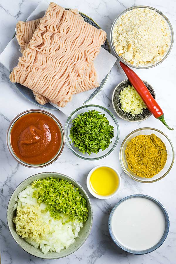 Ingredients for chicken meatball curry, laid out in small bowls.