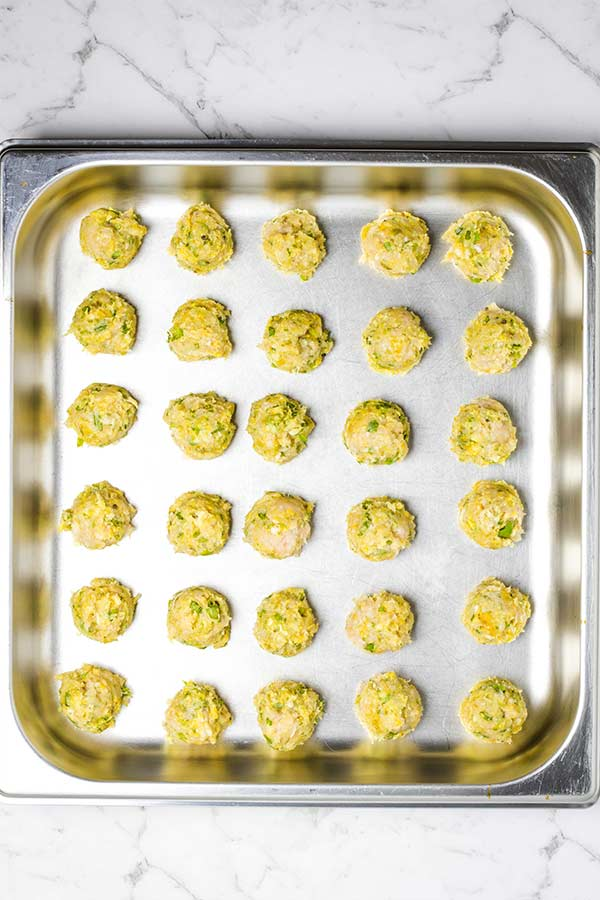 Raw chicken meatballs on a pan, ready for baking.