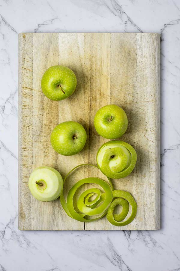 Apples on a wooden board, some peeled and some with skins on.