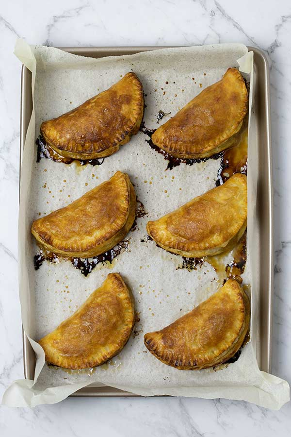 Baked apple turnovers on a tray.
