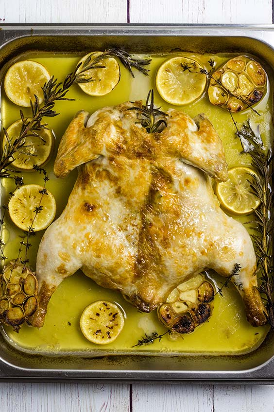 A butterflied roasted chicken in the pan, with garlic and lemon slices, and sprigs of herbs.