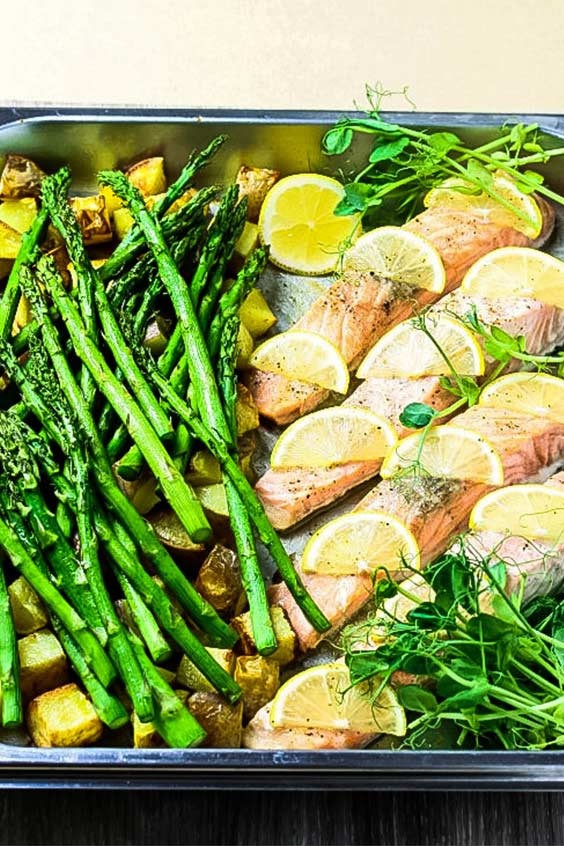 Salmon with lemon slices, baked in a pan with cubed potatoes and asparagus spears.