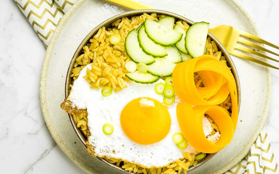 Seasoned Chinese style steamed rice, topped with pickled vegetables and a fried egg.