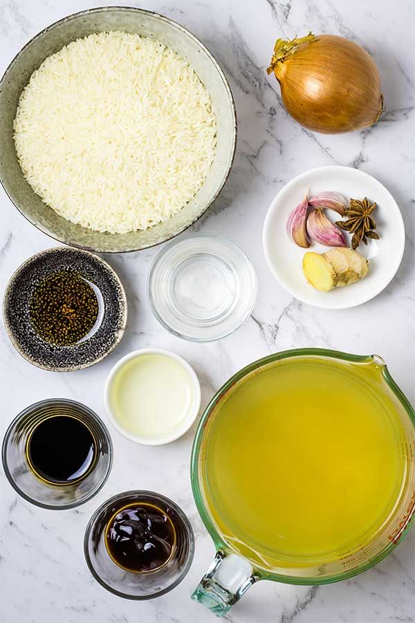 Ingredients for Chinese seasoned steamed rice: onion, garlic, ginger, star anise, sesame oil, soy sauce, oyster sauce, stock.