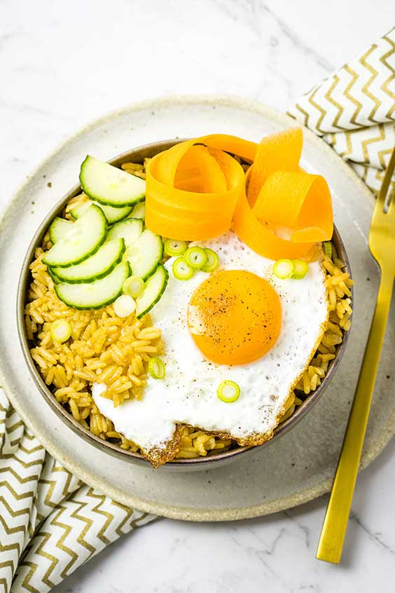 A bowl of Chinese style seasoned rice with a fried egg, cucumber and carrot curls, sitting on a gold zigzag cloth.