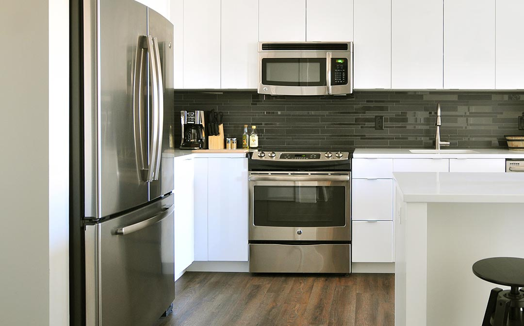 A white kitchen with stainless steel oven, microwave and refrigerator