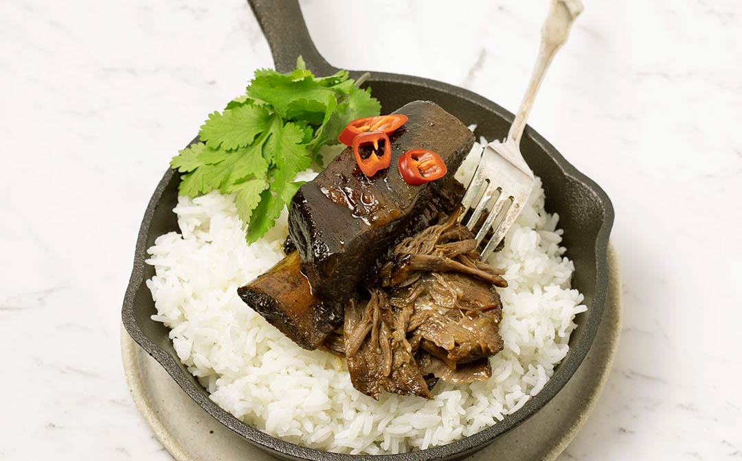 Sticky Asian style beef rib with meat shredded off the bone, served on a bed of rice with cilantro leaves and red chilli.