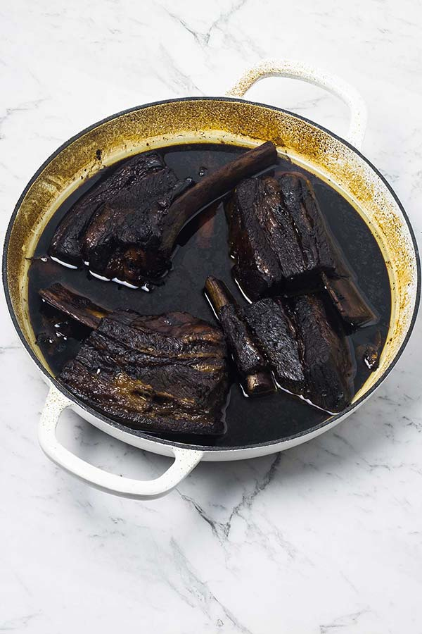 Cooked Asian style sticky beef ribs in a white baking dish.