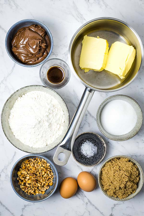 Ingredients for Nutella blondies; Nutella, vanilla, butter, white and brown sugar, eggs, salt, hazelnuts and flour.