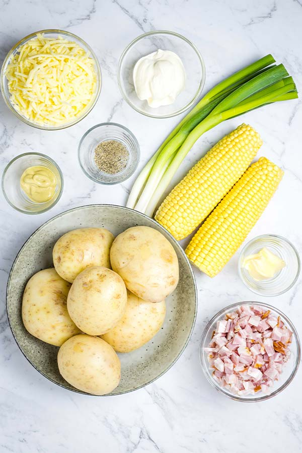 Ingredients for twice baked potatoes, ready to cook: potatoes, bacon, butter, corn, scallions, pepper, mustard, sour cream and cheese.
