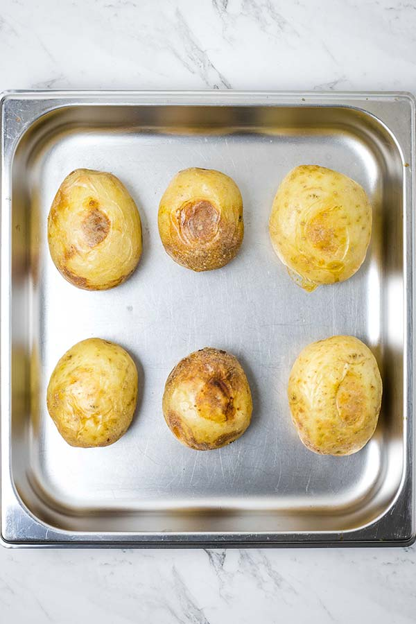 Six roasted potatoes in a metal baking tray.