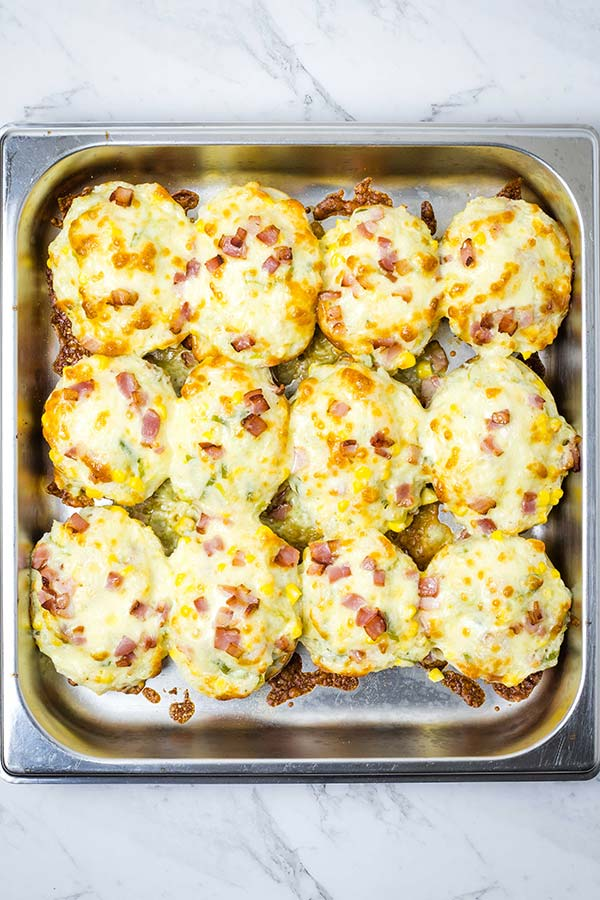 A pan of 12 cooked twice baked potatoes with cheese and bacon sprinkled over the top.