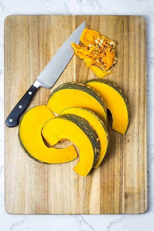 De-seeding and slicing pumpkin into wedges for roasting